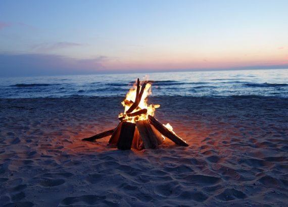 a camp fire on a beach